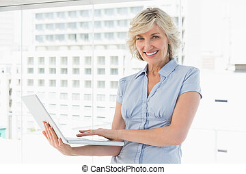 Portrait of a happy businesswoman using laptop in a bright...