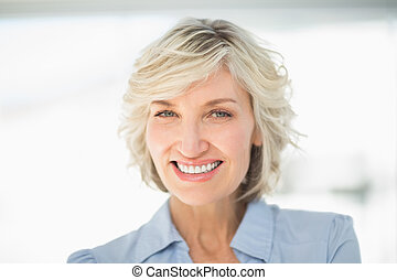 Close-up portrait of a smiling businesswoman against blurred...