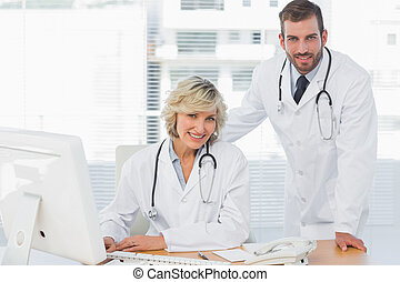 Smiling doctors with computer at medical office