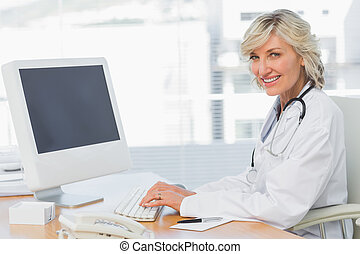 Female doctor using computer at desk in medical office -...