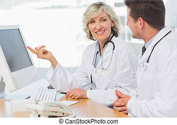Doctors using computer at medical office - Two concentrated...