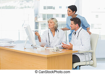 Doctors using computer together at