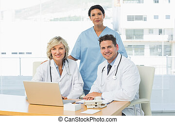 Smiling doctors with laptop at medi - Portrait of three...