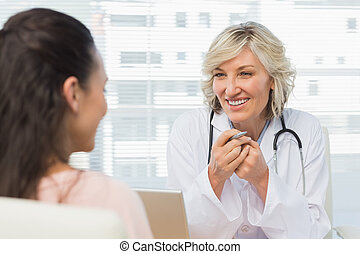 Friendly female doctor in conversation with patient in the...