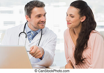 Male doctor showing something on laptop to patient in...