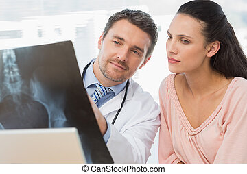 Male doctor explaining x-ray report to patient - Male doctor...