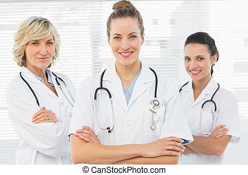 Three confident female doctors with arms crossed - Portrait...