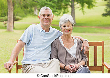 Senior couple sitting on bench at park - Portrait of a...