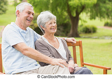 Side view of senior couple sitting on bench at park - Side...