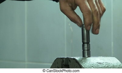 Atomizing nozzle. Close-up - Worker repairing atomizing...