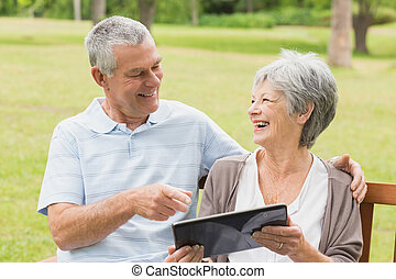 Cheerful senior couple using digital tablet on bench at park...