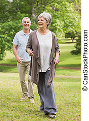 Happy senior couple walking in park - Full length of a happy...