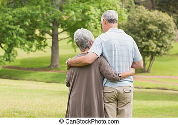 Rear view of senior couple with arms around at park - Rear...