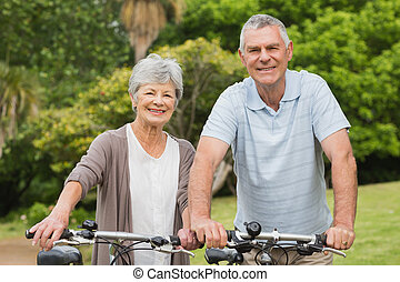 Senior couple on cycle ride at park - Portrait of a senior...