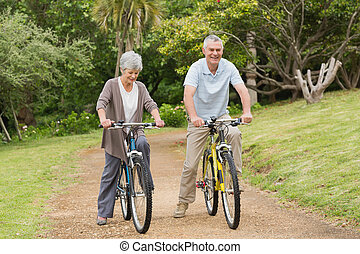 Senior couple on cycle ride in countryside - Full length of...