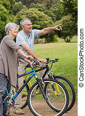 Senior couple on cycle ride in countryside - Side view of a...