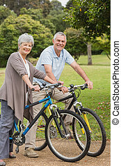 Senior couple on cycle ride in countryside - Side view...