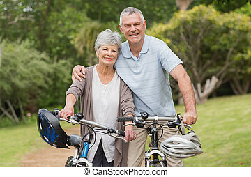 Senior couple on cycle ride at the park - Portrait of a...