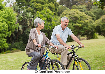 Senior couple on cycle ride in coun - Side view of a senior...