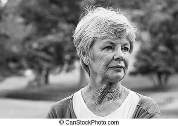Senior woman looking away at park - Close-up of a senior...