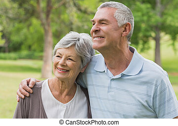 Smiling senior couple with arms around at park - Smiling...