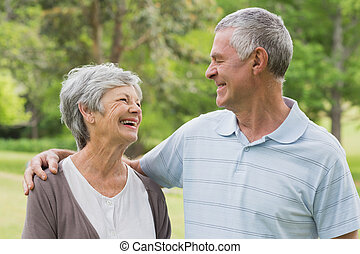 Happy senior couple with arms around at park - Happy senior...