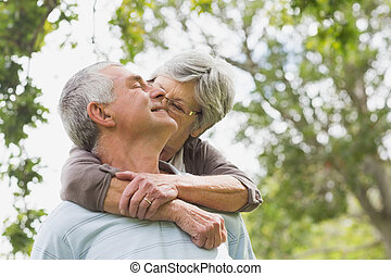 Senior woman embracing man from behind at park