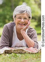 Close-up of a senior woman lying at park