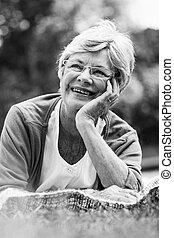 Smiling senior woman lying at park - Close-up of a smiling...