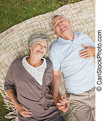 Smiling relaxed senior couple lying in park - High angle...