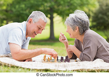 Happy senior couple playing chess at the park - Side view of...