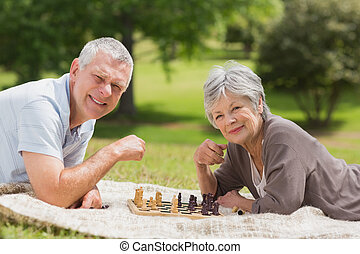 Happy senior couple playing chess a