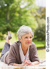 Thoughtful senior woman lying at park - Thoughtful senior...