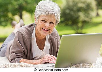 Smiling senior woman using laptop a