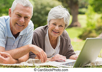Smiling senior couple using laptop at park - Smiling senior...
