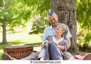 Senior man embracing woman from behind at park