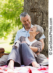 Happy relaxed senior couple sitting at park - Happy relaxed...