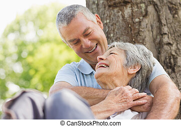 Senior man embracing woman from behind at park - Close-up of...