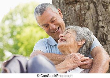 Senior man embracing woman from behind at park - Close-up of...