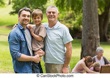 Grandfather, father and son with family in background at park