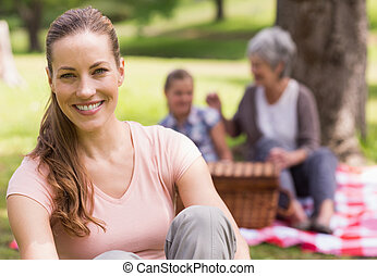 Woman with grandmother and granddaughter in background at park