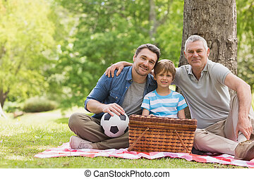 Grandfather, father and son with picnic basket at park -...