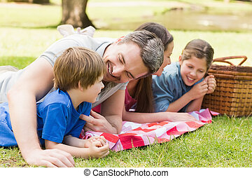 Smiling couple with young kids lying in park