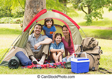 Couple with kids sitting in the tent at park - Portrait of...
