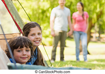 Kids in tent with couple in background at park - Portrait of...