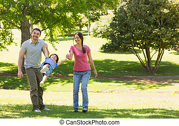 Family of three holding hands at park