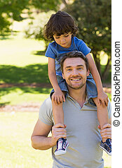 Smiling man carrying son on his shoulders in park - Portrait...