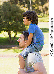 Smiling man carrying son on his shoulders in park - Side...