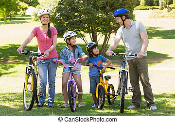 Family of four with bicycles in park - Full length a family...