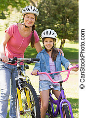 Woman with her daughter riding bicycles - Portrait of a...